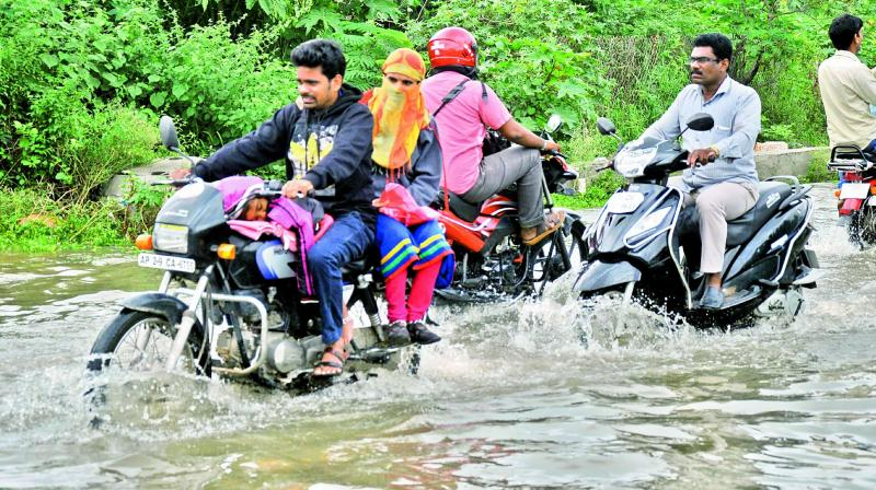 Motorists negotiate a flooded road in Nacharam on Tuesday. (Photo: DC)