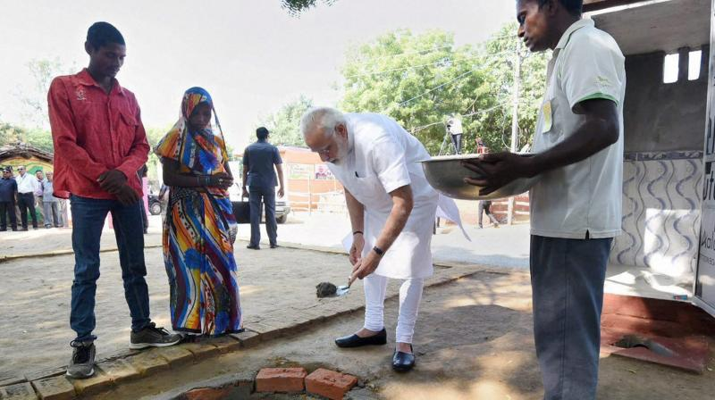 Prime Minister Narendra Modi doing shramdan for the construction of a twin pit toilet, at Village Shahanshahpur, Varanasi, Uttar Pradesh on Saturday. (Photo: PTI)