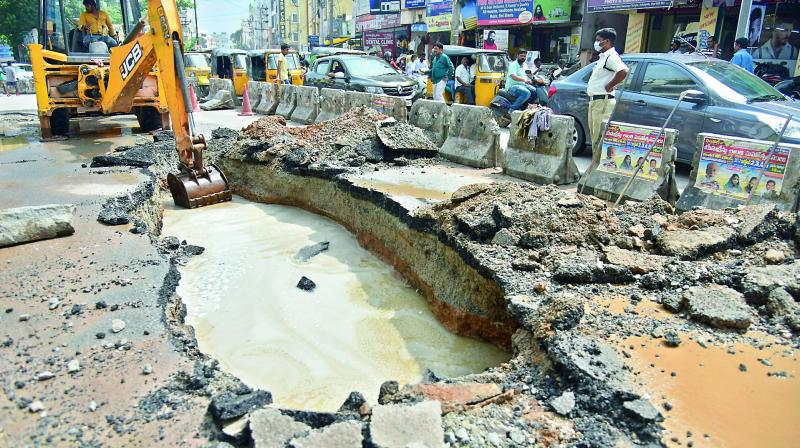 An earthmover was pressed into service after a portion of the road caved in at Usha Mullapudi Road, Kukatpally, following heavy rains on Sunday.  (Photo: S. Surender Reddy)