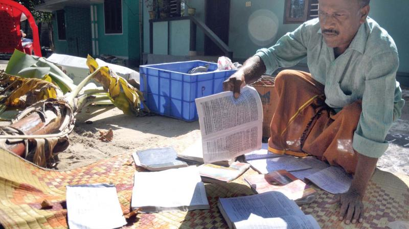 A father puts his daughter's books, soaked in flood waters, to dry in the sun at cyclone-ravaged Chellanam in Kochi on Wednesday. The daughter is in a relief camp. (Photo: SUNOJ NINAN MATHEW)