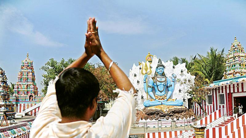 A devotee prays at the painted and decorated Shiva temple at Kurubarahalli ahead of the Shivaratri festival in Bengaluru on Monday. (Photo: DC)