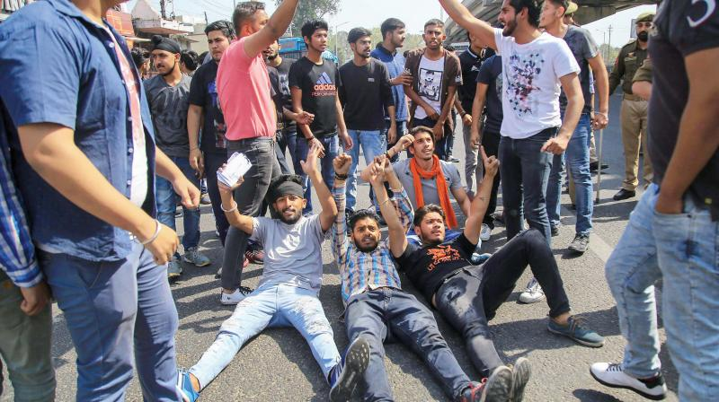 Students block a road during a protest against CBSE paper leak, in Jammu on Saturday. (Photo: PTI)