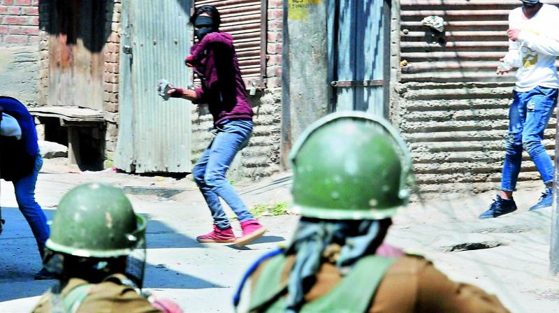 A man throws stones on security personnel during clashes following Shopian encounters, in Srinagar on Sunday. (Photo: PTI)