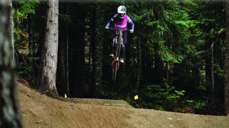 Anita Naidu performs a stunt on her mountain bike.