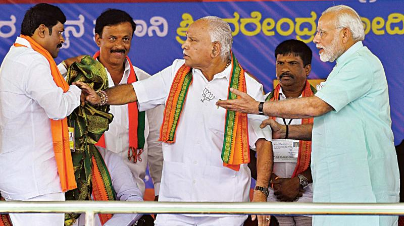PM Narendra Modi pacifies state BJP president B.S. Yeddyurappa after an altercation on stage at the election rally at Santhemarahalli near Chamarajanagar on Tuesday. (Photo:AP)