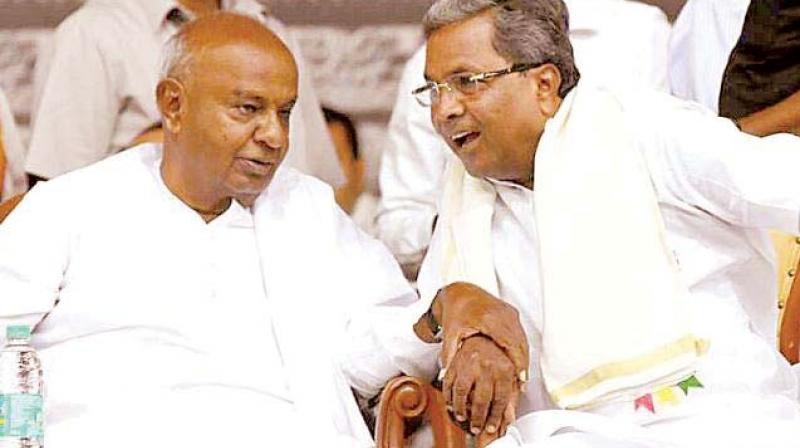 A file picture of JD(S) chief H.D. Deve Gowda with senior Congress leader Siddaramaiah.