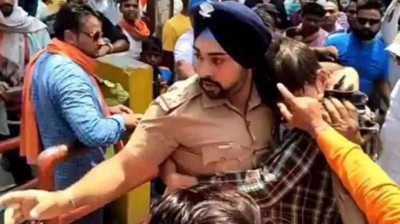 Inspector Gagandeep Singh and the Muslim youth he saved from the mob in Ramnagar last week. 	File pic