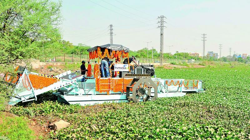 Floating trash collector removes water hyacinth and other floating material at Chandan Cheruvu at Jillelaguda. (Image DC)