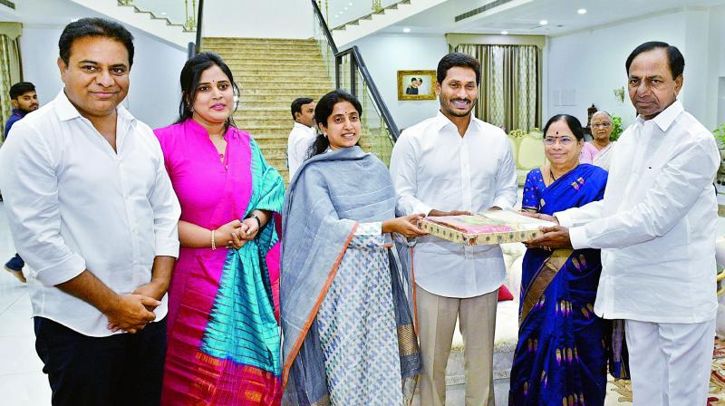 Chief Minister K. Chandrasekhar Rao and family offer sweets to Andhra Pradesh Chief Minister-designate Jagan Mohan Reddy when they visited his house on Saturday to invite him for the swearing-in ceremony.
