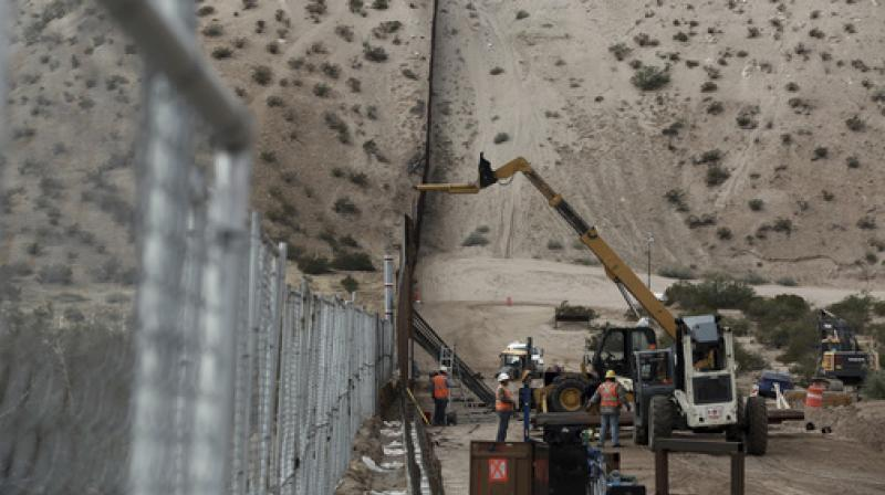 In this file photo, workers continue work raising a taller fence in the Mexico-US border area separating the towns of Anapra, Mexico and Sunland Park. (Photo: AP)