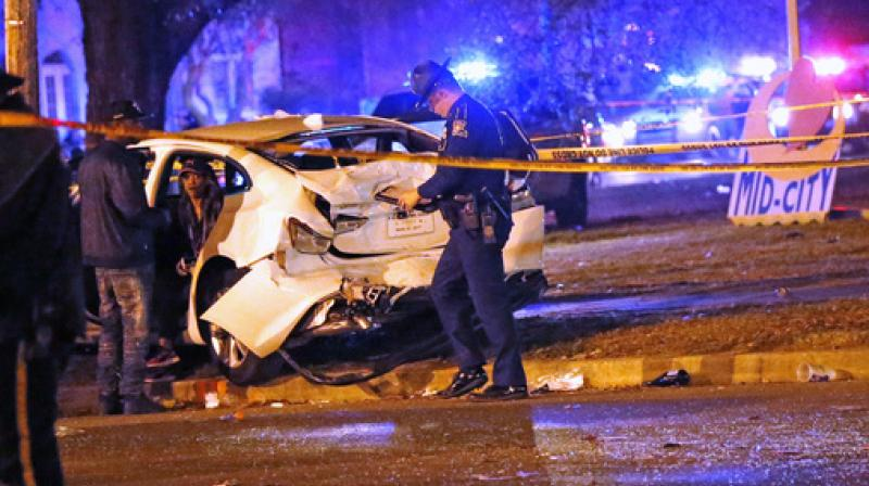 Police talk to a man sitting in a car that was struck by a pickup truck, that slammed into a crowd and other vehicles, causing multiple injuries, during the Krewe of Endymion parade in New Orleans. (Photo: AP)