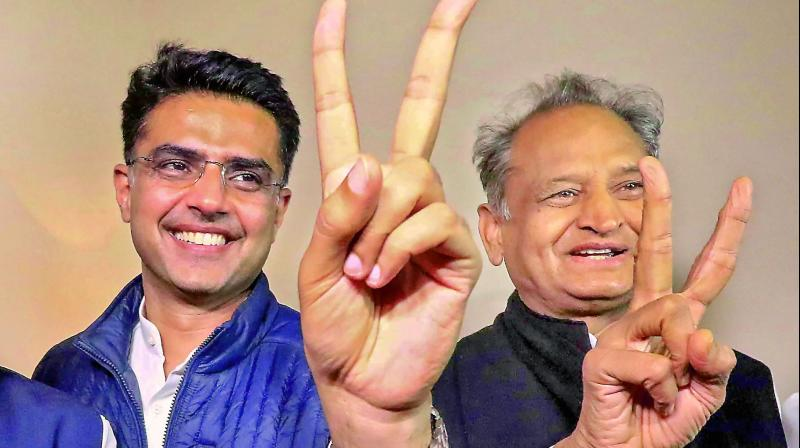 Congress leaders Ashok Gehlot (R) and Sachin Pilot (C) flash victory signs after the declaration of Rajasthan Assembly election result, in Jaipur on Tuesday. — PTI