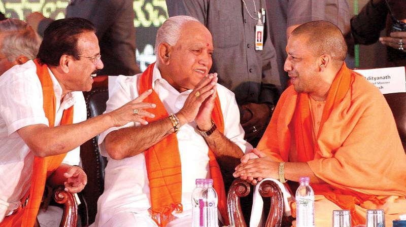 Uttar Pradesh Chief Minister Yogi Adityanath (from R), BJP state president B.S. Yeddyurappa and Union Minister D.V. Sadananda Gowda at the party's Parivarthana Rally in Bengaluru on Sunday (Photo: Shashidhar B)