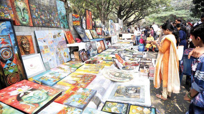 People throng the annual fair of exhibits, art work and art performance at Chitra Sante at Karnataka Chitrakala Parishath on Kumara Krupa Road in Bengaluru on Sunday. (Photo: DC)