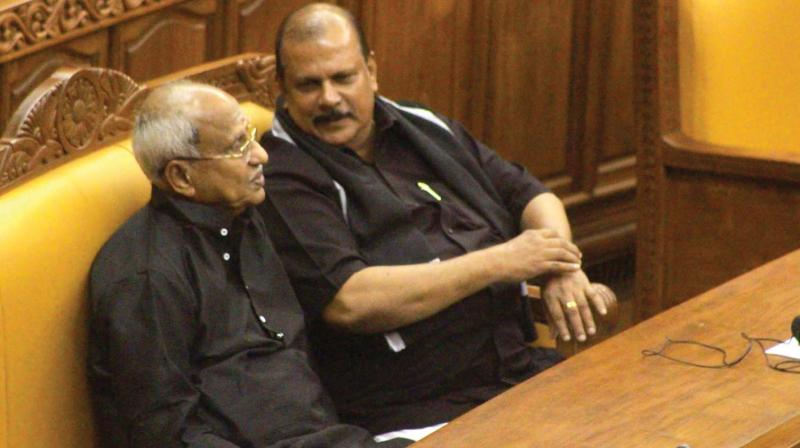 P. C. George having a word with BJP legislator O Rajagopal in House on Wednesday. Both came to the Assembly wearing black dress as a mark of protest against the prohibitory orders clamped by the government in Sabarimala.
