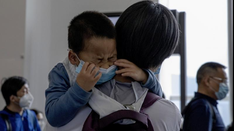 A child cries as he waits in line to board a plane for Beijing at the airport in Hong Kong (AP)