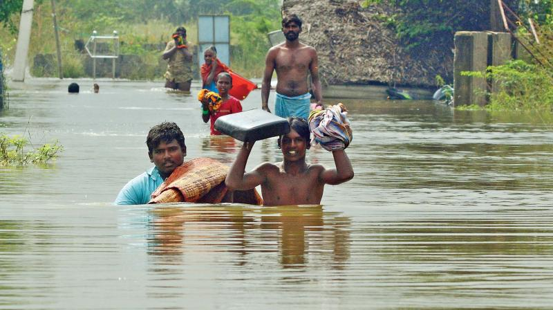 People carrying their things on their heads in chest deep water in Annai Anjugam Nagar, on Kishkinta road. in Tambaram. (DC)