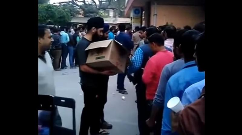 Some members of the Sikh community have come to the common man's rescue by distributing tea and biscuits to the public queuing outside banks and ATM kiosks. (Credit: YouTube)