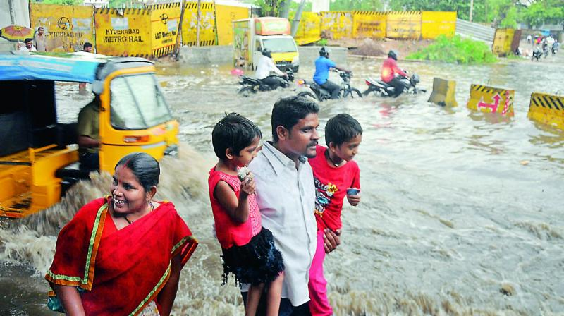 People walk in a flooded road in Bhoiguda, Secunderabad, on Friday. (Photo: Deepak Deshpande)