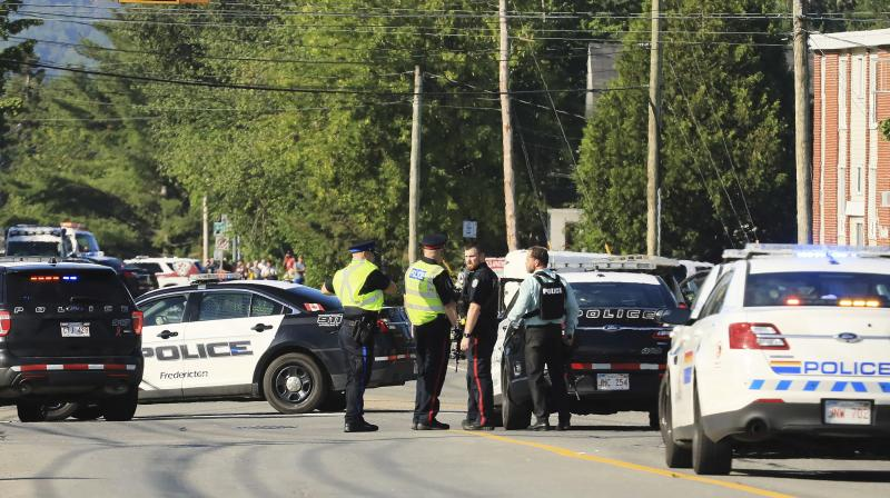 Police officers survey the area of a shooting in Fredericton, New Brunswick, Canada on Friday. (Photo: AP)