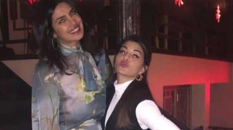 Priyanka wore a blue jumpsuit with floral prints and neon heels while Jacqueline was in a black and white dress.