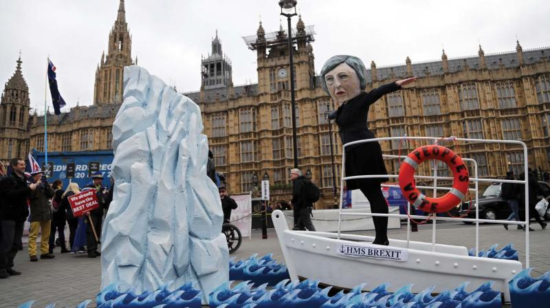 An activist from Avaaz wears a mask of Britain's Prime Minister Theresa May as Pro-European demonstrators protest opposite the Houses of Parliament in London on Tuesday.  (Photo: AP)