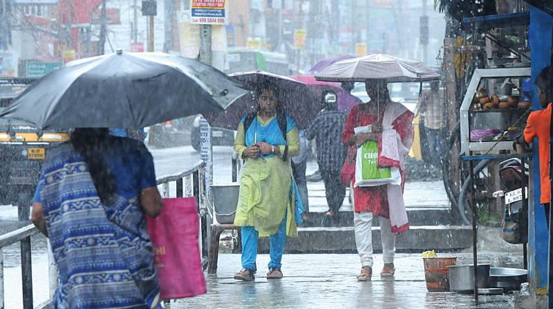 People move through the streets of Kochi amidst monsoon rains. ARUNCHANDRA BOSE