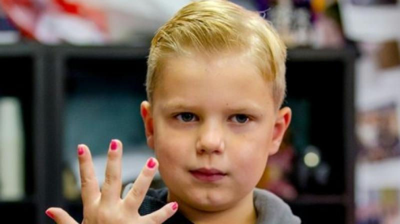 Tijn, a 6-year-old boy, shows his painted nails as he raises money during the