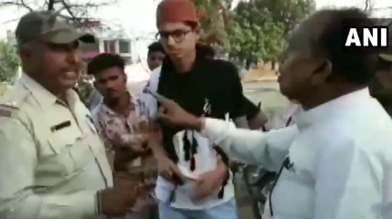 In the video, the cop is trying to explain Veer Singh Bhuria, a Congress lawmaker that he issued challan as the motorcyclist was triple-riding without a number plate but Bhuria goes on to support the lawbreakers. (Photo: Twitter I ANI)