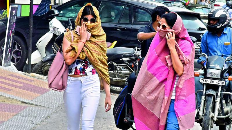 Women use scarves to save themselves from heat wave on Sunday. (Photo: Pavan)