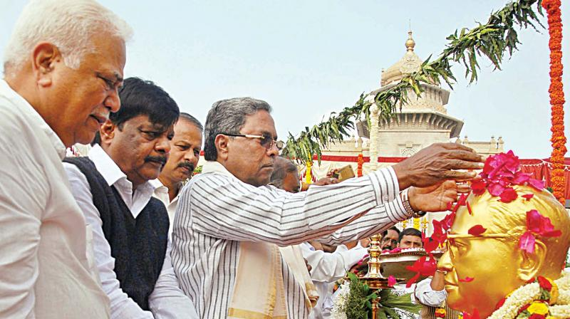 Chief Minister Siddaramaiah garlands the statue of Dr B.R. Ambedkar at Vidhana Soudha in Bengaluru on Wednesday as ministers RV Deshpande and Dr H.C. Mahadevappa look on. (Photo: DC)