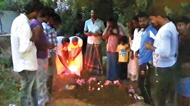 Villagers offer prayers at the monkey's grave.  (DC)