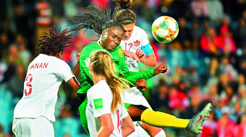 Cameroon's Marlyse Ngo Ndoumbouk  (centre) vies for the ball with Canada's  Kadeisha Buchanan in a Women's World Cup Group 'E' match at the Mosson Stadium in Montpellier on Tuesday. (Photo: AFP)