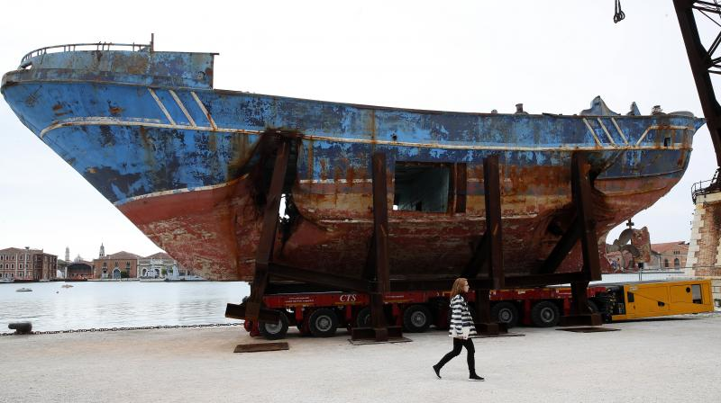 A woman walks past the wreck of the 'Barca Nostra' fishing boat, which sank in the Mediterranean Sea in 2015 with 700 migrants on board, displayed at the 58th Biennale of Arts exhibition in Venice, Italy. (Photo: AP)