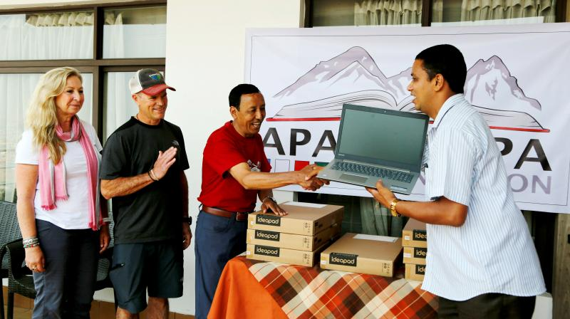 Apa Sherpa (centre) hands over a computer to Chakra Karki, representative of a school from Dhuske, Okhaldhunga district in Kathmandu, Nepal. (Photo: AP)