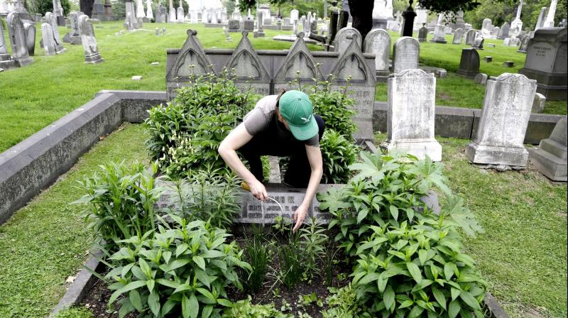 Volunteer Jennifer Walker clears an area as she plants on the Keen family plot at the Woodlands Cemetery in Philadelphia. (Photo: AP)