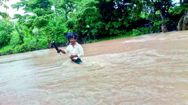 A resident of the Mamidiguda (G) village wades though floodwater to reach his village from Indravelli mandal head quarters in the Adilabad district on Tuesday. (Photo: DC)