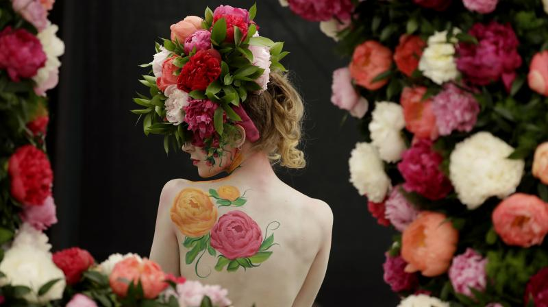 A model is seen with peony design body paint and a hat made of peonies. (Photo: AP/Matt Dunham)