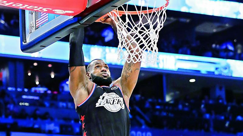 LeBron James dunks against Stephen Curry during the NBA All-Star game in Charlotte on Sunday (Photo: AP)