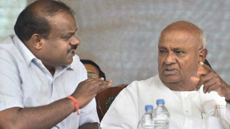 A file photo of former chief minister H.D. Kumaraswamy and his father and party supremo H.D. Deve Gowda at a party workers' meeting.