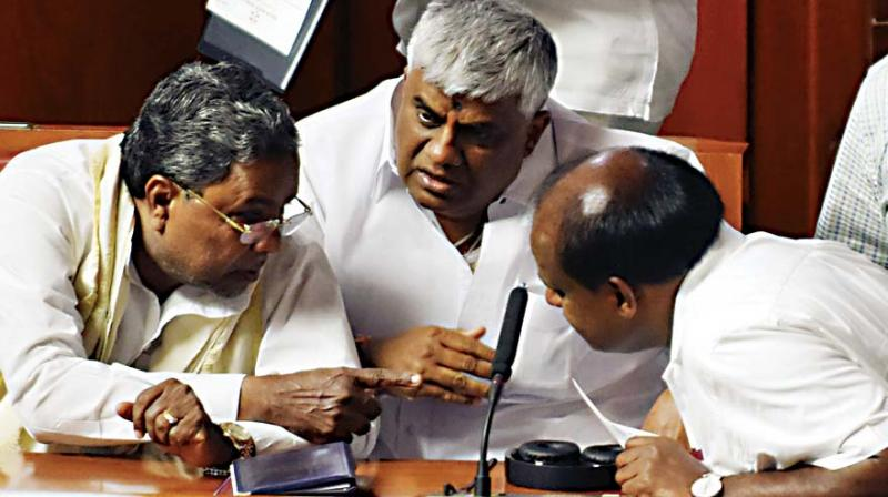 Chief Minister H.D. Kumaraswamy, former CM Siddaramaiah and PWD Minister H.D. Revanna in discussion during the legislature session on Wednesday