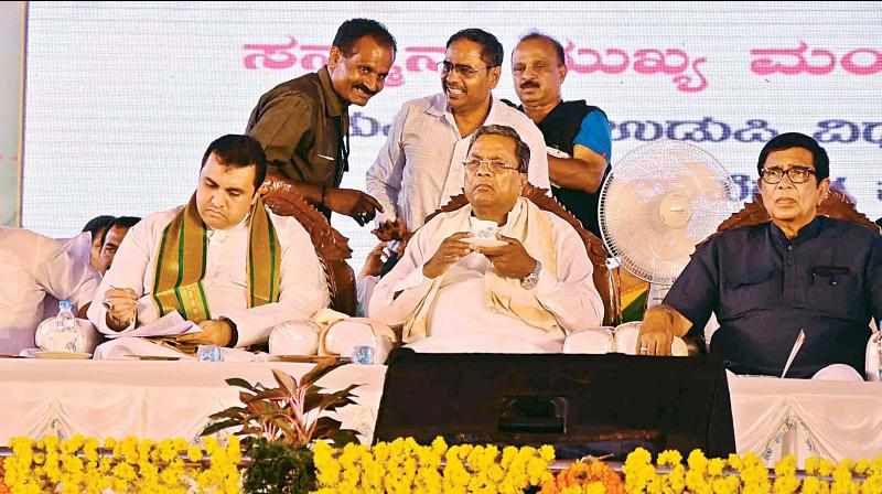 Minister for Fisheries Pramod Madhwaraj CM Siddaramaiah and Congress MP Oscar Fernandes at a function in Brahmavara in Udupi district on Monday