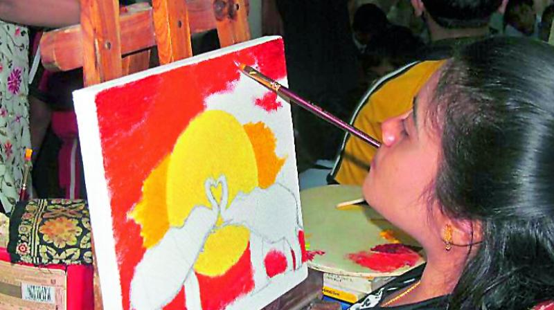 Srilekha painting with a brush in her mouth.