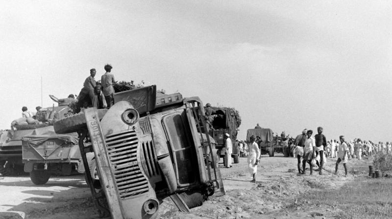 The Indian Army moves past an overturned truck of the Hyderabad Army on September 17, 1948.  Picture courtesy Mohammed Safiullah.
