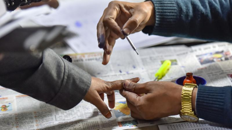 A polling official applies indelible ink on the finger of a voter during the Delhi Assembly elections at Old Rajinder Nagar polling station, in New Delhi on Saturday. PTI photo