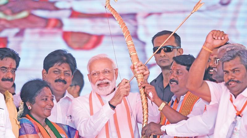 Prime Minister Narendra Modi being presented a bow and an arrow during an election campaign rally in Ramanathapuram, on Saturday. (PTI)