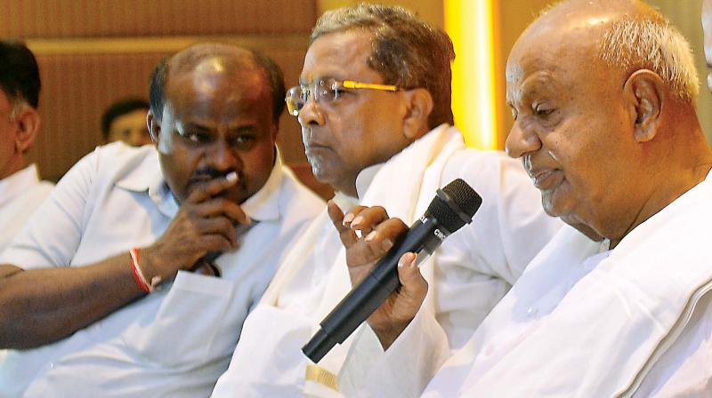 CM H.D. Kumaraswamy has a word with former CM Siddaramaiah even as former PM H.D. Deve Gowda speaks at Congress-JD(S) press meet in Bengaluru on Saturday. (Sathish B.)