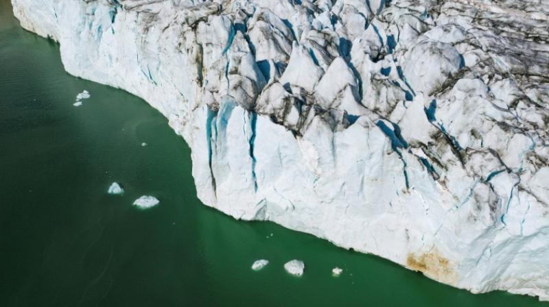 Skimming low over the gleaming white glaciers on Greenland's coast in a modified 1940s plane, three NASA scientists, led by an Elvis-impersonating oceanographer, waited to drop a probe into the water beneath them. (Photo: AFP)