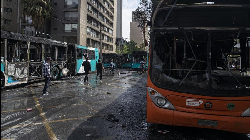 Buses that were set alight by demonstrators during last night's protests stand on a street in Santiago, Chile, Saturday, Oct. 19, 2019. (Image: AP)