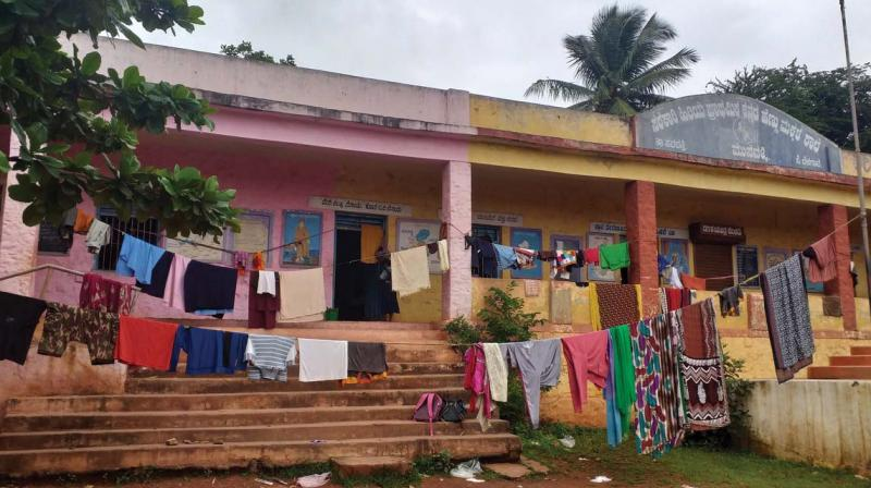 Flood victims hang their washed clothes to dry outside the school in Munavalli town, Savadatti in Belagavi.